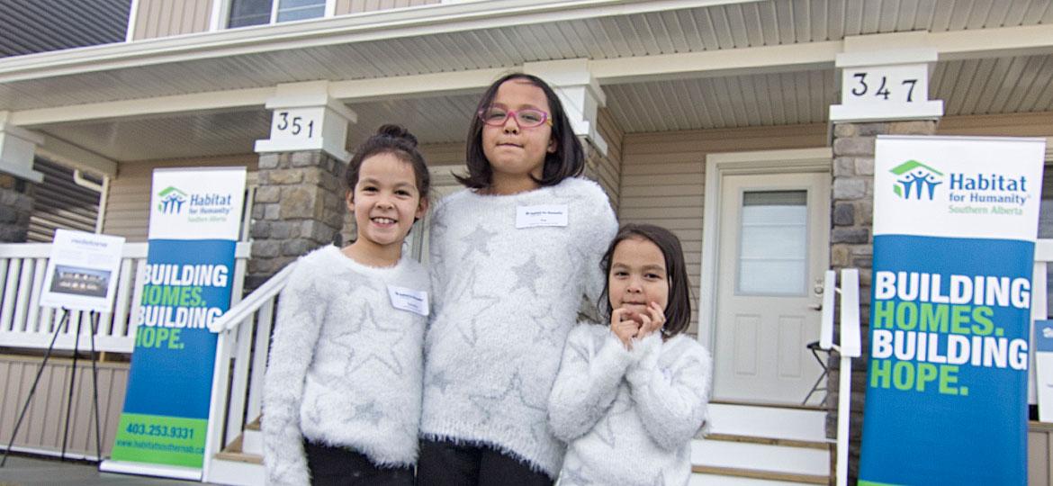 family in front of their new Habitat home